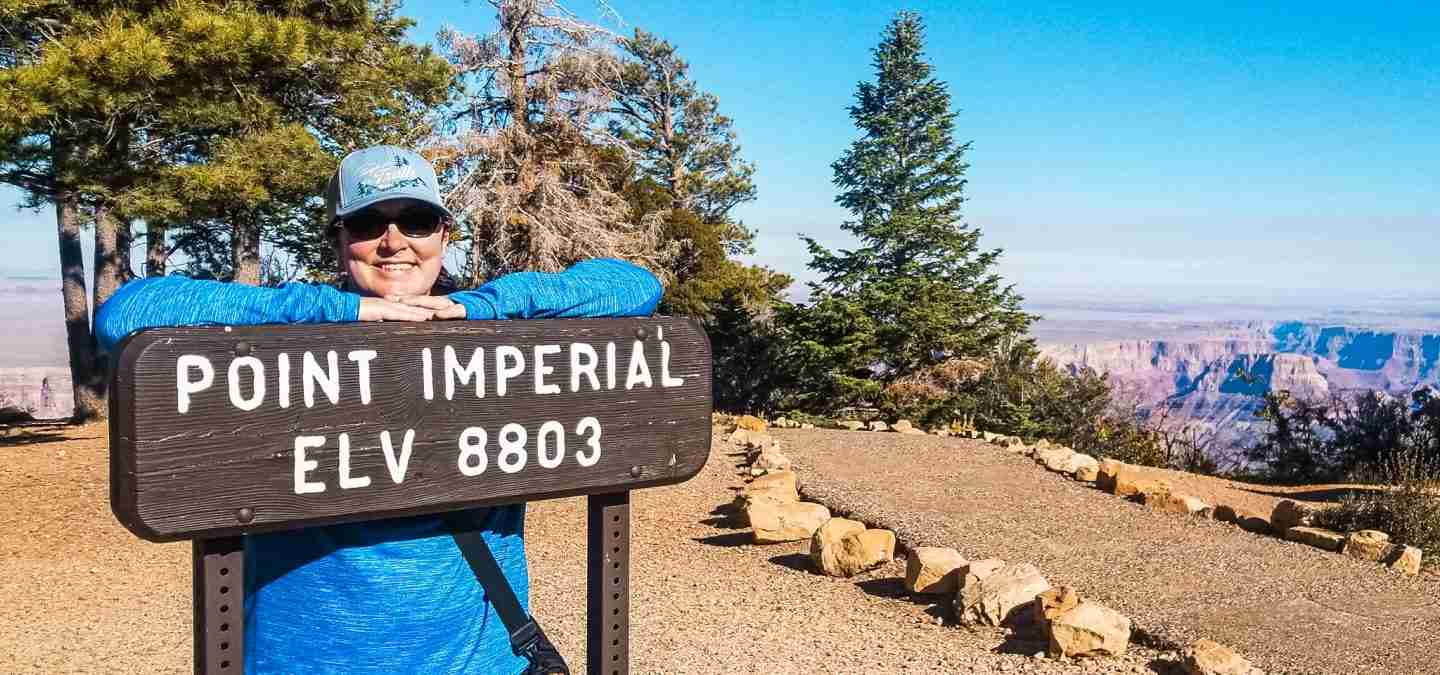 "Woman smiling behind a sign that reads ""Point Imperial Elv 8803."""
