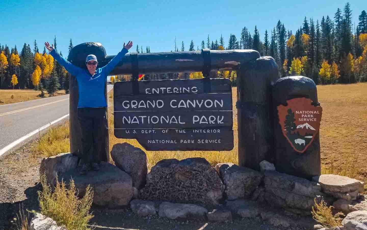 "White woman in a blue shirt and dark pants standing excitedly at the ""Grand Canyon National Park"" Entrance Sign for the North Rim with golden Aspens in background."