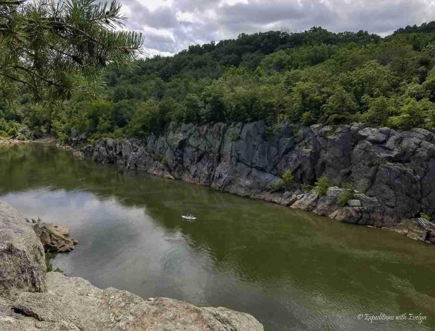 A kayaker exploring outdoors on a river off between rocky gray cliffs on the Billy Goat A Trail in Great Falls Park.