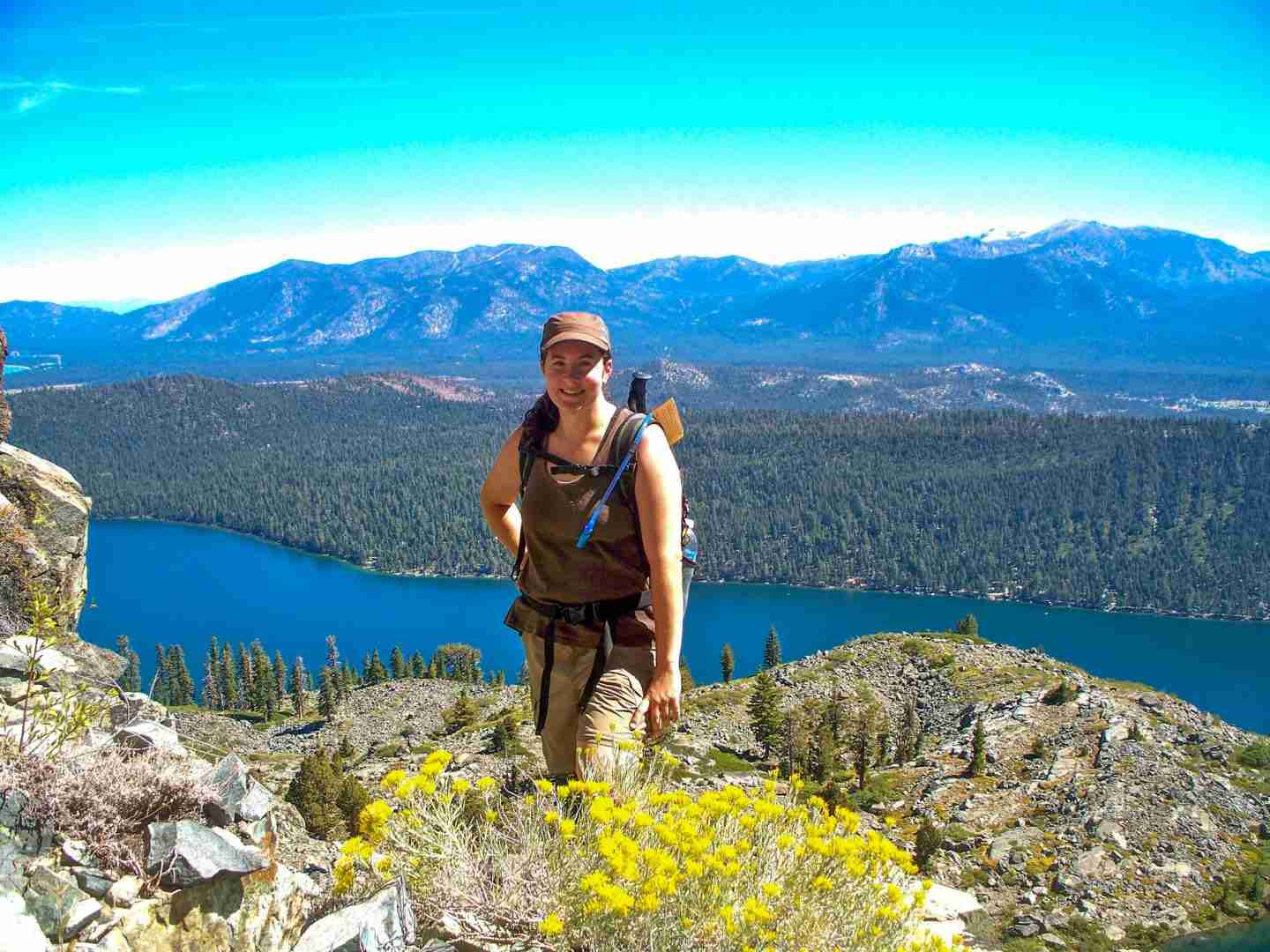 I love that hiking make me smile like this.  A female hiker poses on top of a mountain standing behind yellow flowers with Lake Tahoe and mountains behind her.