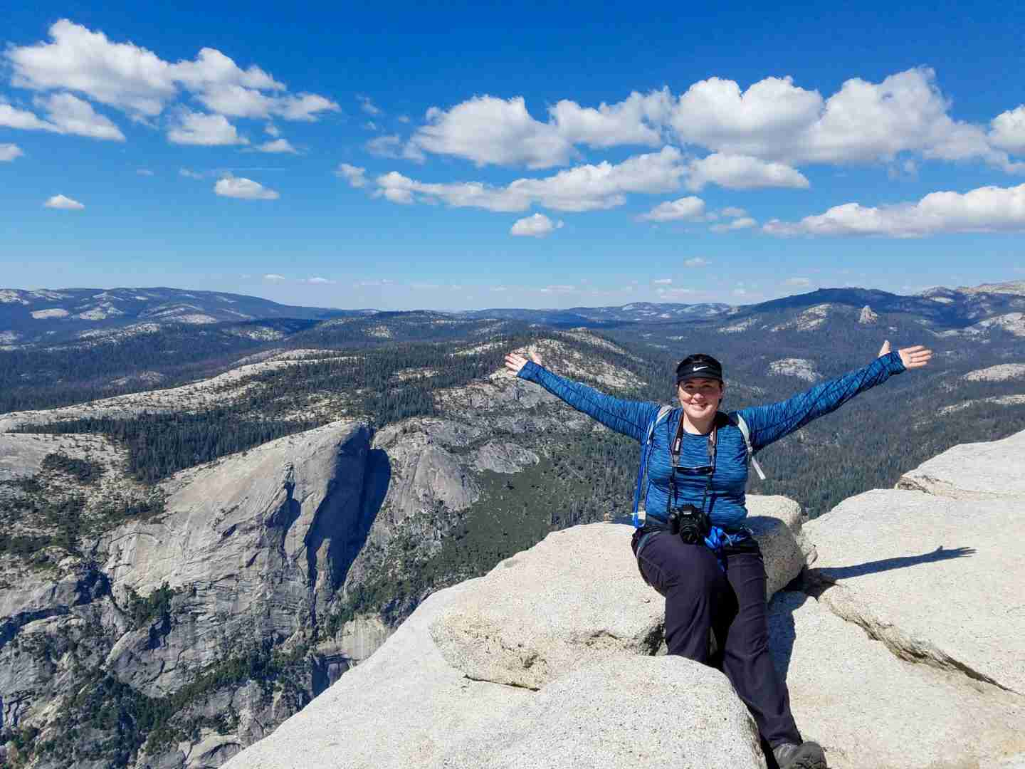 A female hiker in a blue shirt and black pants sits on granite rock with her arms outstretched high above granite rocks of Yosemite Valley.
