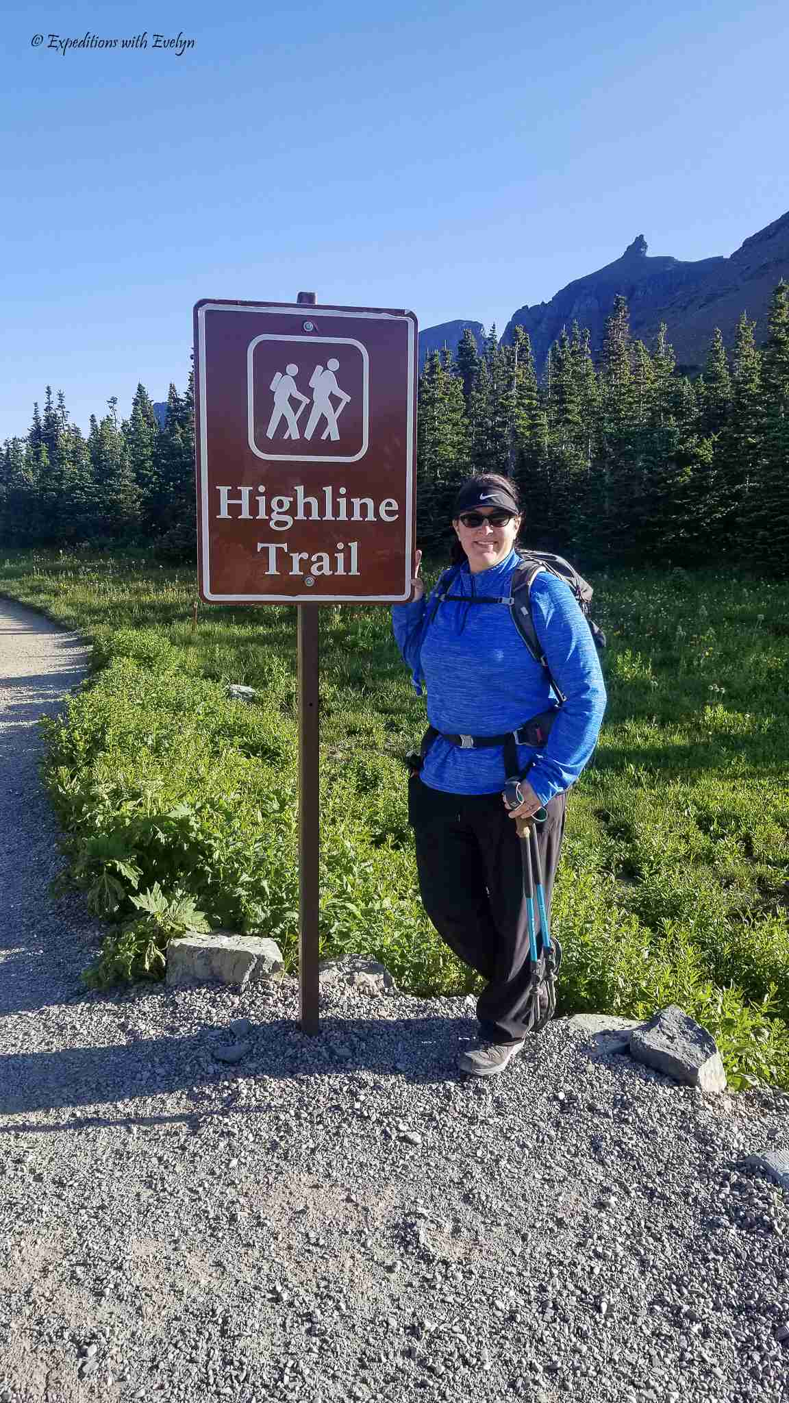 """A female hiker in a blue shirt, black pants, and backpack, poses at a trailhead side with white letters reading """"Highline Trail""""."""