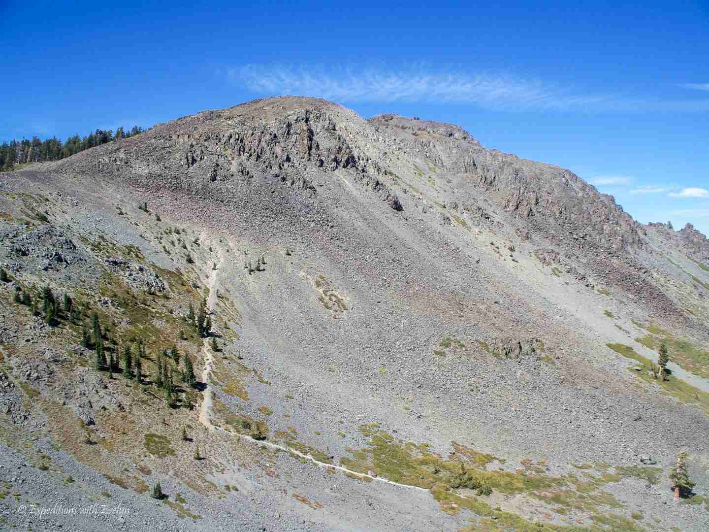 A trail zig zags up a barren side of a gray mountain.
