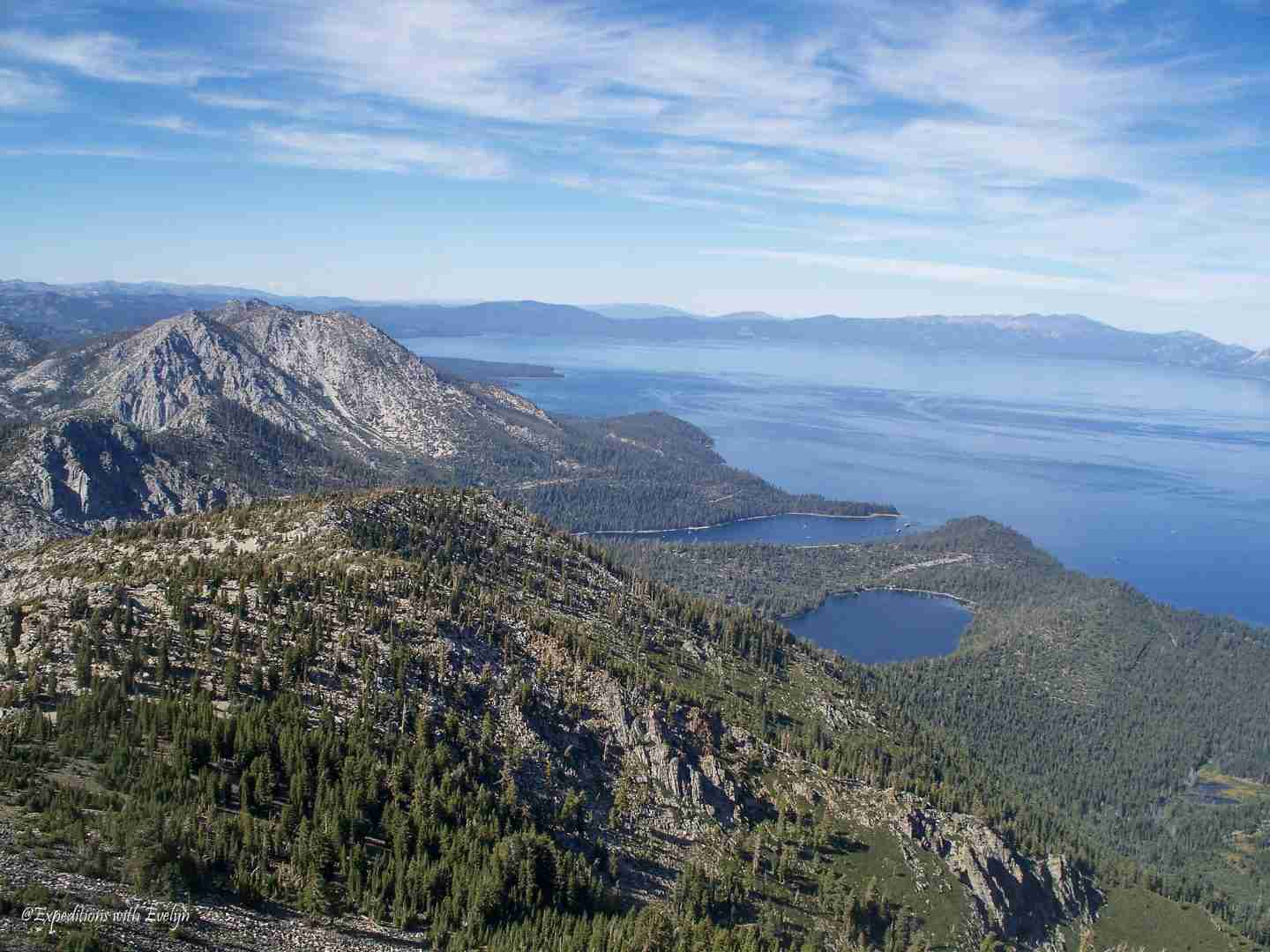 Sapphire blue Lake Tahoe and other lakes and inlets surrounded by other gray mountains covered in pine trees from the summit of Mount Tallac.