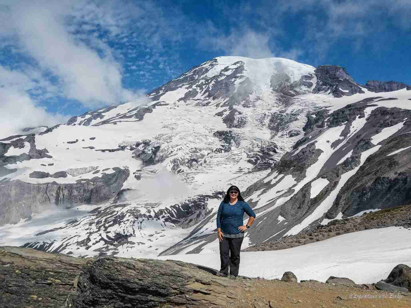 A female hiker poses in front of the snow covered Mount Rainier volcano with blue sky and light clouds.