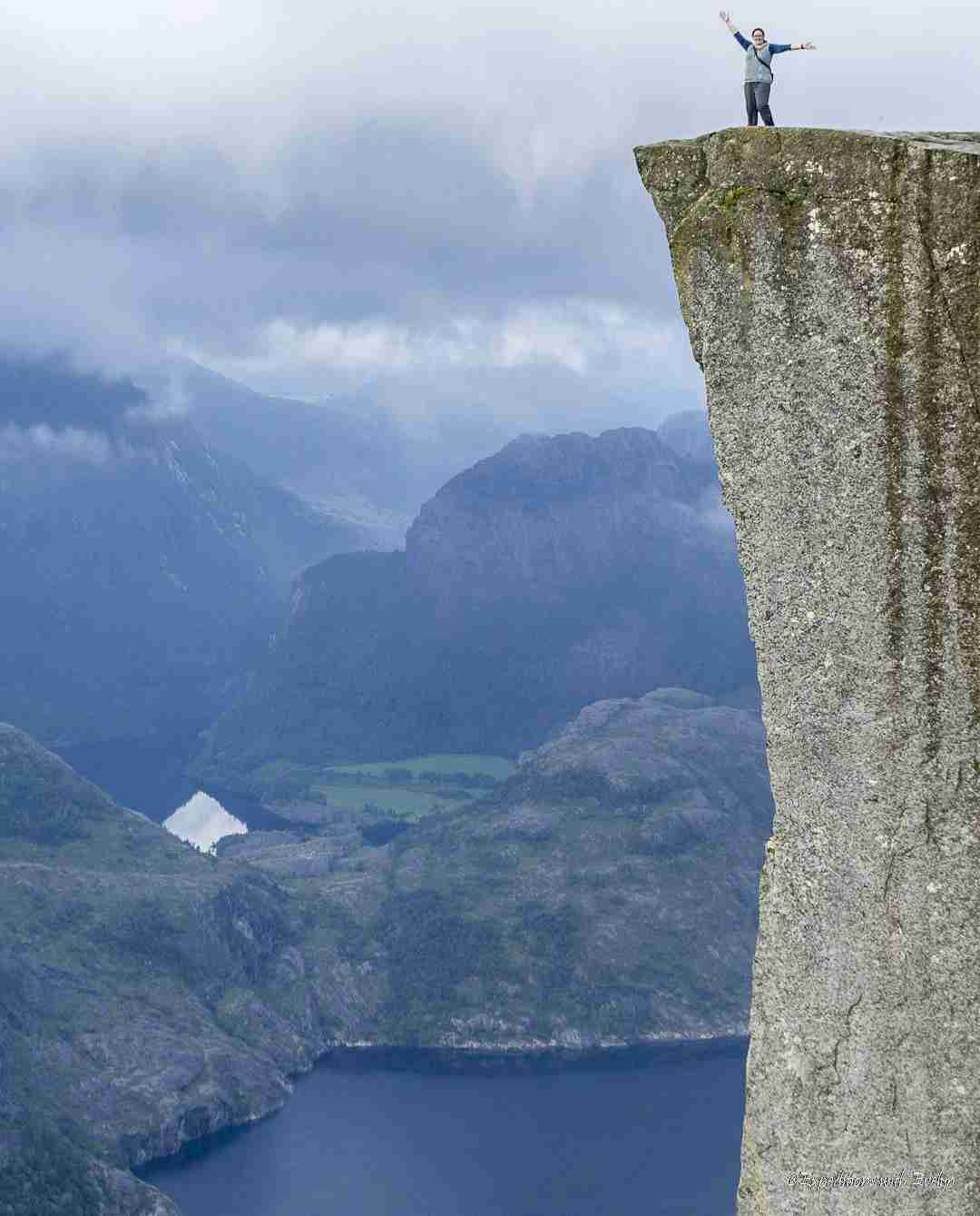 A hiker stands on top of a 1982  foot high gray rock that juts out above a deep blue Norwegian fjord.