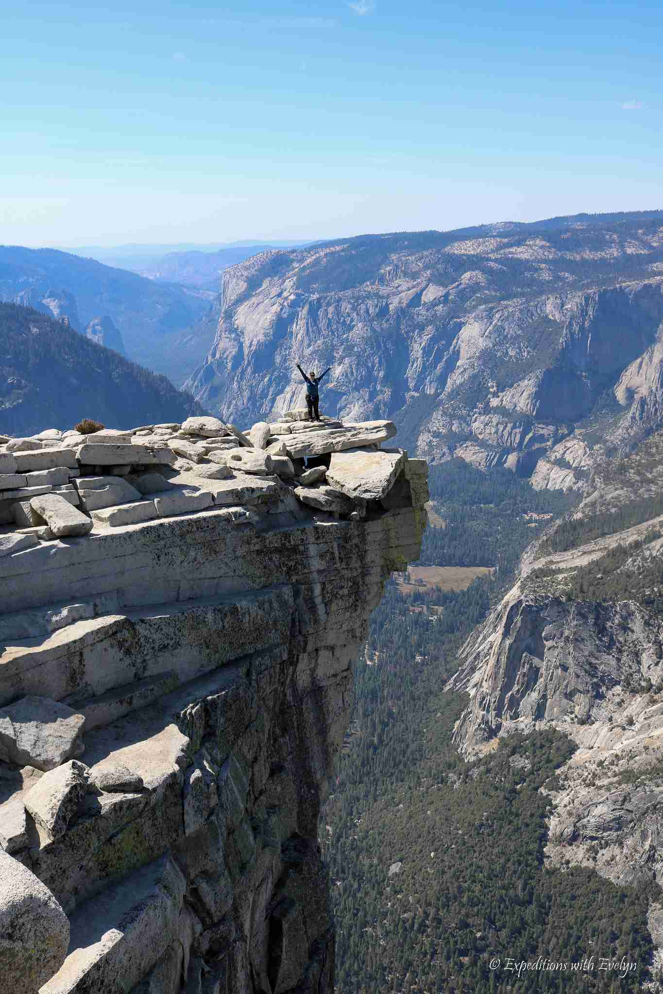 A hiker stands on top of the granite summit of Half Dome after completing one of the best hikes in the world.