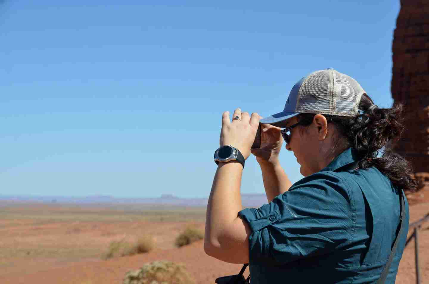 A female hiker demonstrates what to bring hiking for sun protection by wearing a UV-resistant shirt and a hat as she takes a photo in the desert.