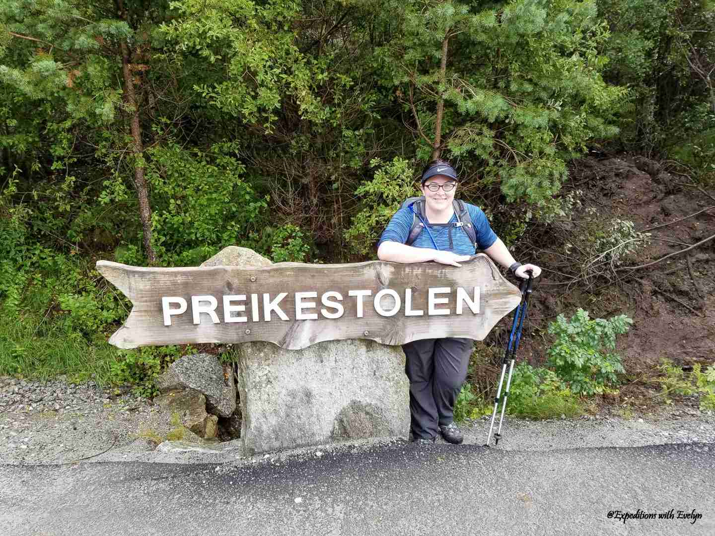 """A female hiker poses behind a brown sign with white letters that reads """"Prekiestolen.""""  She is holding trekking poles."""